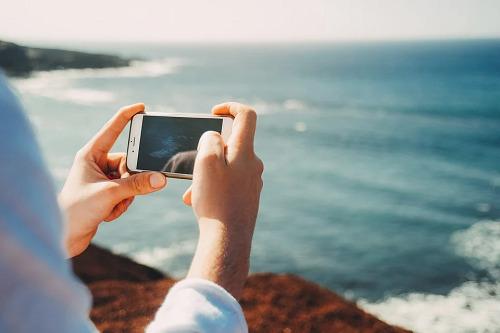 海辺でiPhoneでビデオを見る人